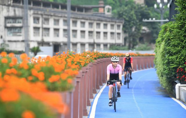 7月23日,市民在重庆市江北区北滨路漫行步道的自行车道上骑行。新华社图。